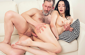 Man copulates a sweet brunette from behind.